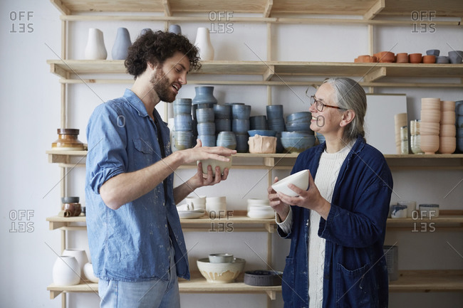 Man and woman discussing over bowl in pottery class
