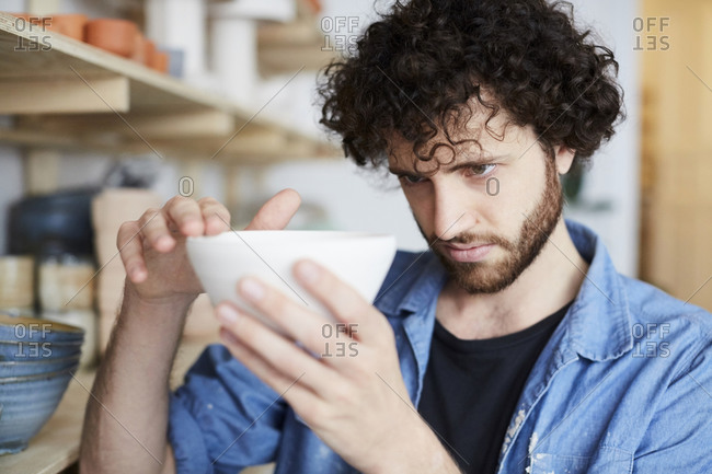 Man examining bowl in pottery class