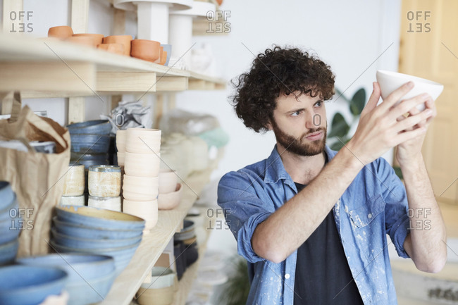Mid adult man examining bowl in pottery class