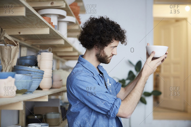 Side view of man looking at bowl in art studio