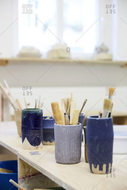 Various paintbrushes in containers on table at workshop