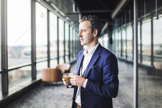 Male entrepreneur with hot drink standing in office corridor