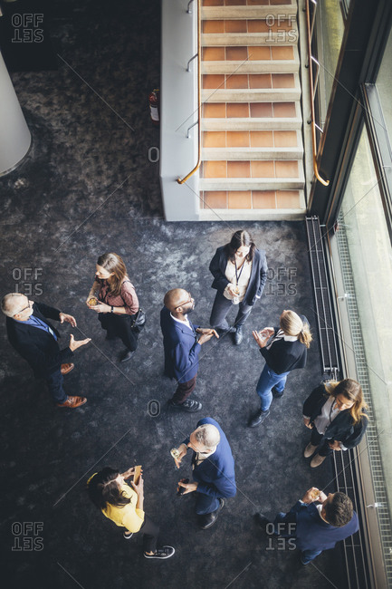 High angle view of business people discussing while standing at workplace