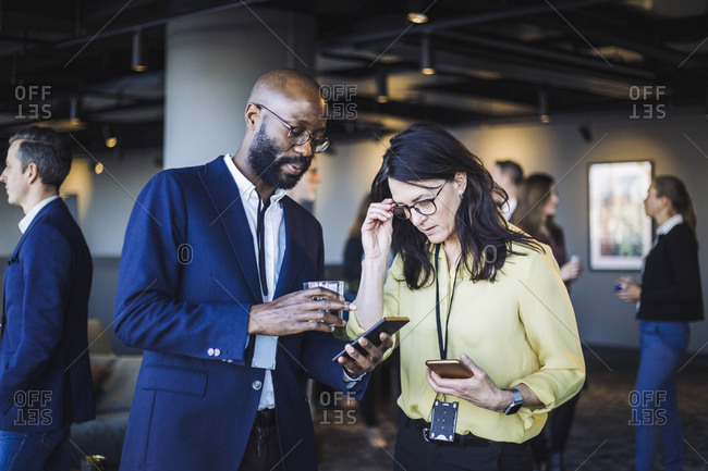 Male entrepreneur showing smart phone to female colleague in office