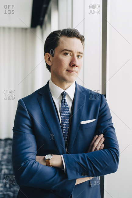 Portrait of confident businessman with arms crossed standing at workplace