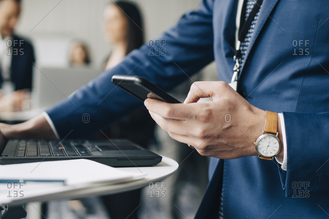 Midsection of businessman using phone while standing in office seminar