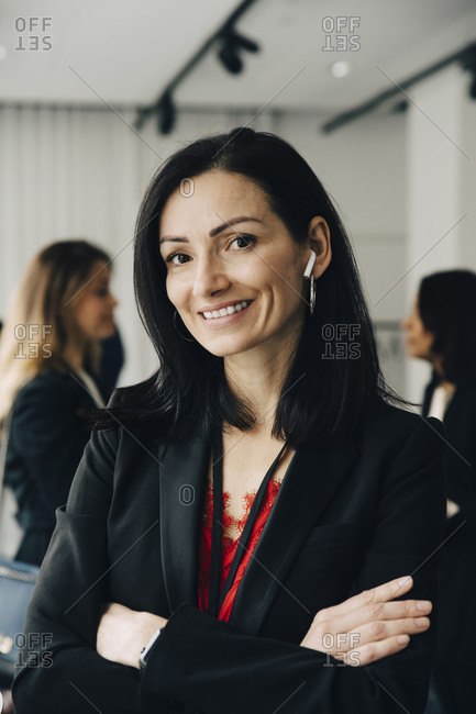 Portrait of businesswoman with arms crossed at workplace