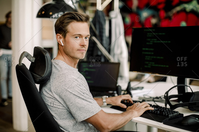 Portrait of male computer programmer working in office