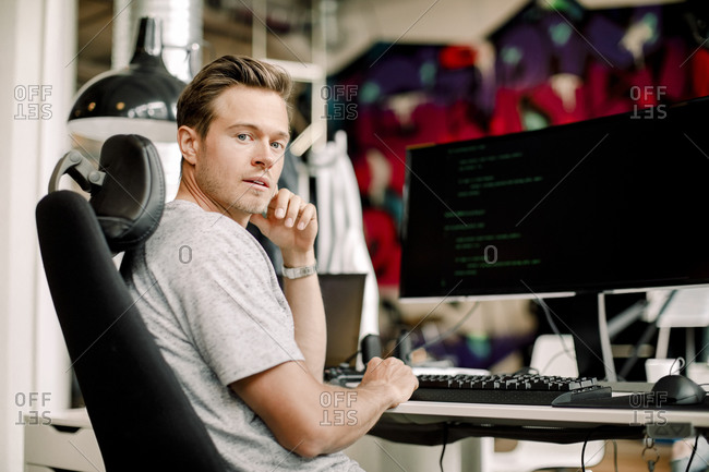 Portrait of male computer programmer sitting in office