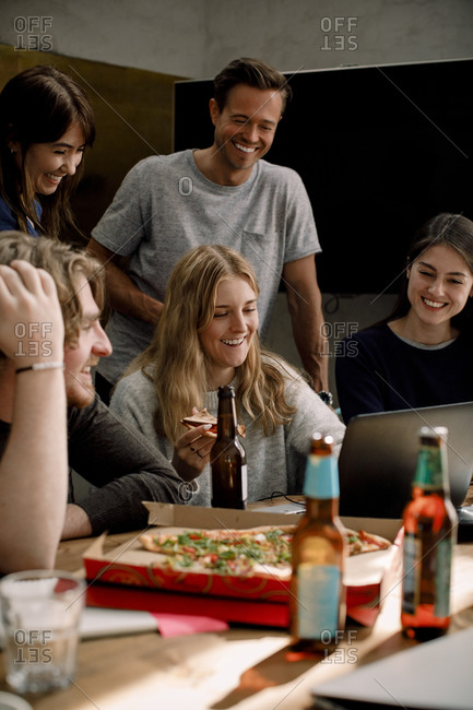 Smiling professionals eating pizza and working in office