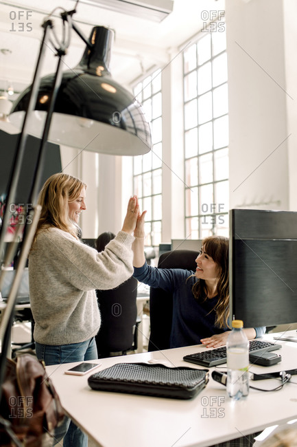 Smiling female colleagues giving high-five at workplace