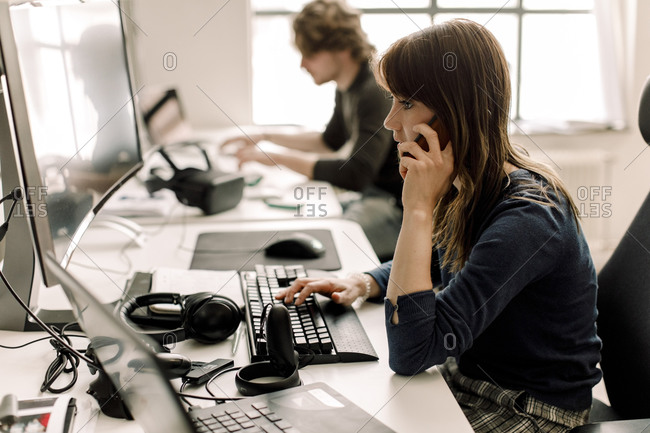 Female entrepreneur working on computer while talking on phone at workplace