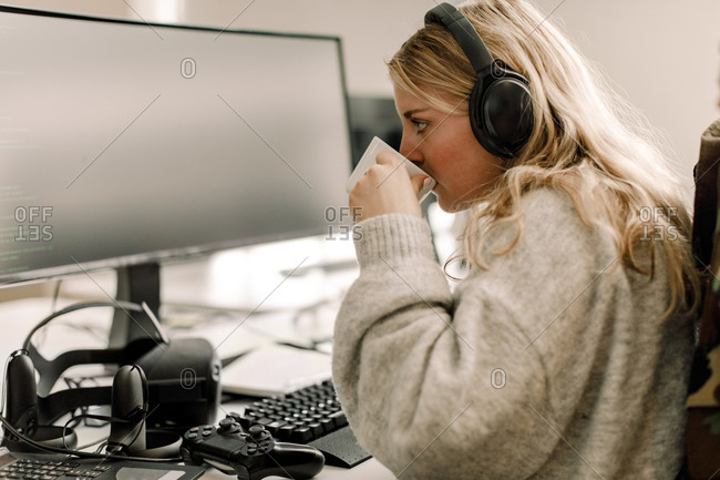Side view of businesswoman drinking coffee while working on computer in office