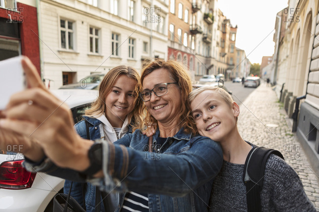 Smiling mother and children taking selfie through smart phone at roadside during weekend