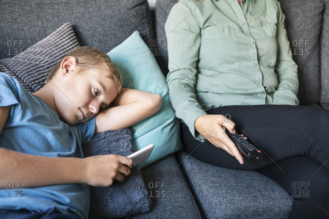 Midsection of woman holding remote control while son using phone on sofa