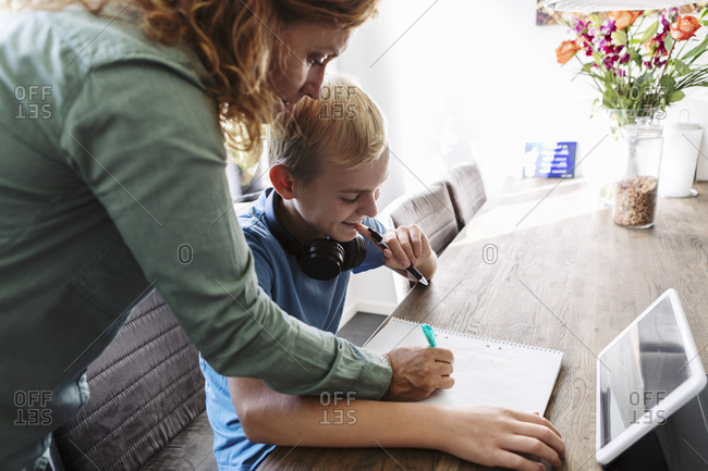 Mother helping smiling son in studying at home