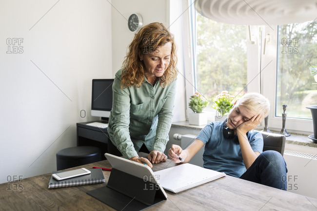 Mother helping son study at home