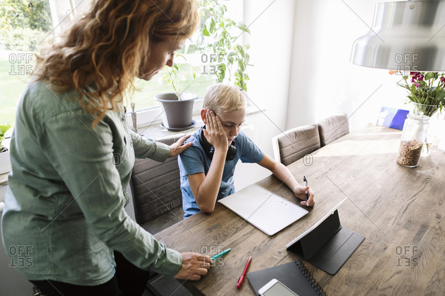 High angle view of mother looking at son studying by table