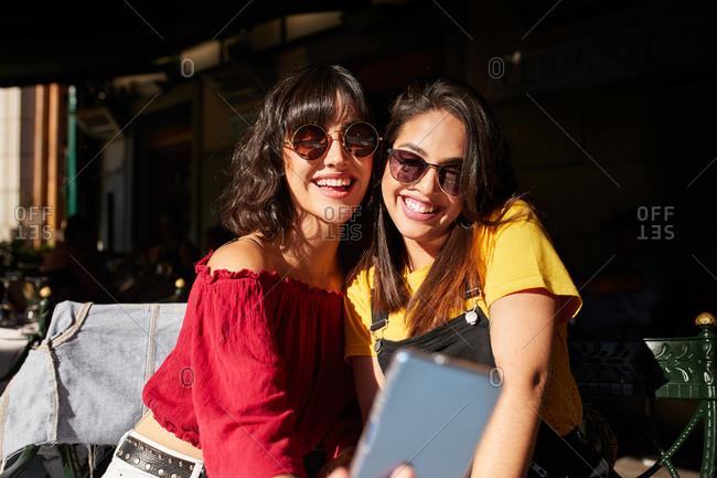 Two teenage girls taking a selfie wearing sunglasses