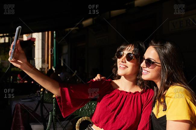 Teen girls taking a selfie wearing sunglasses