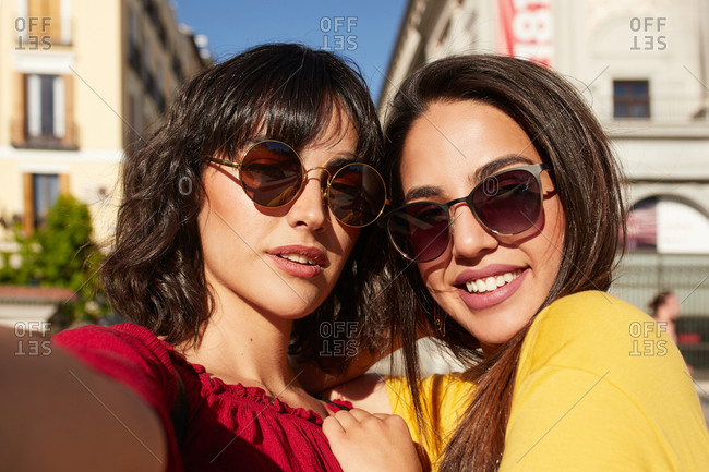 Selfie of two teenager girls smiling and looking at the camera wearing sunglasses