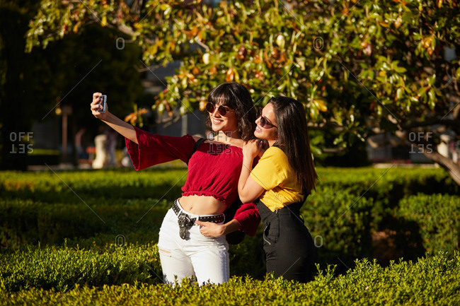Teenager girls taking a selfie on a sunny day while wearing sunglasses