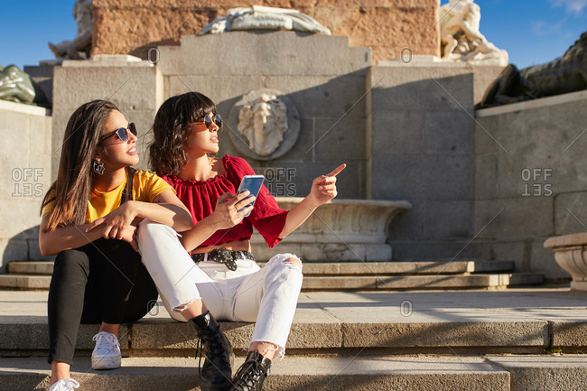 Teenage girls sitting down and one is pointing at something in the distance in Madrid, Spain