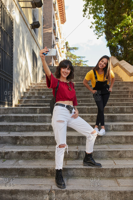 Teen girls walking down city stairs and taking a selfie