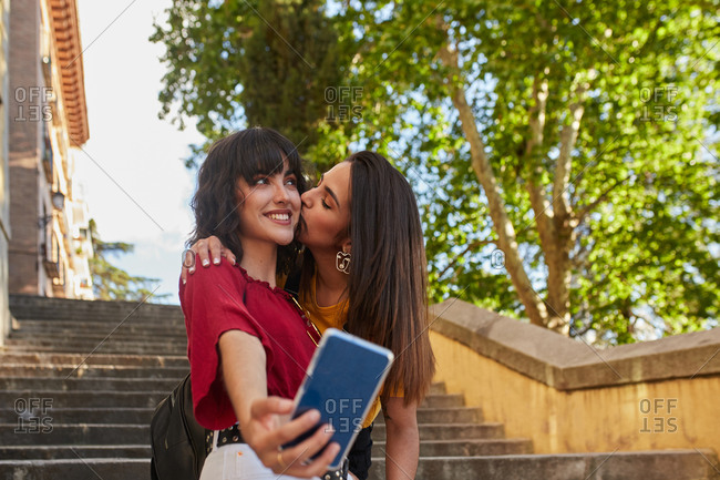 Girls standing stairs and taking a selfie with one kissing the other on the cheek
