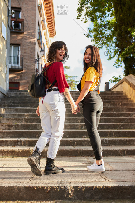 Two teenage girls walking up stairs looking back at the camera and holding hands