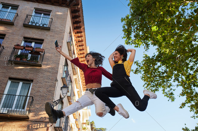 Teen girls jumping up and taking a selfie mid air