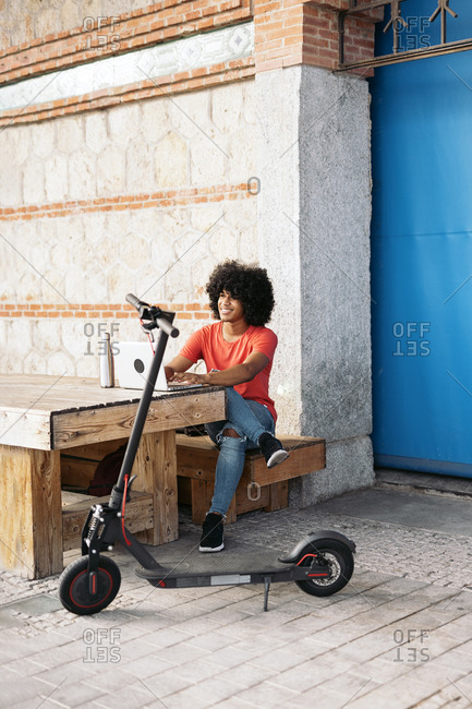 Happy black boy using a laptop while sitting in a wooden table by his electric scooter