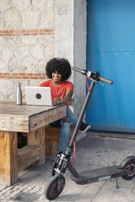 Smiling teen black boy using a laptop while sitting in a wooden table by his electric scooter