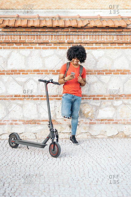 Happy black boy with an afro using his phone and leaning on wall by an electric scooter