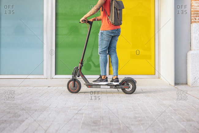 Low-section of boy riding electric scooter