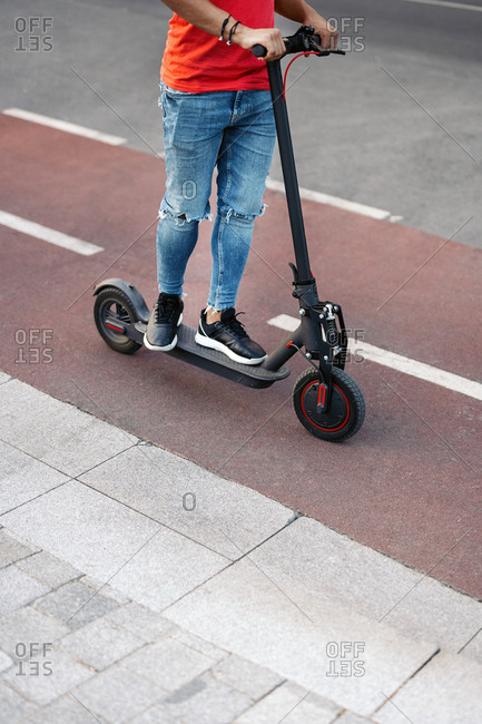 Low-section of a boy riding electric scooter
