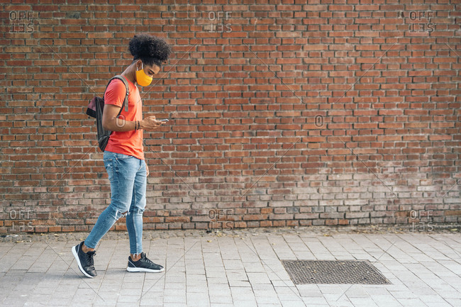 Black boy looking at his phone while walking and wearing a face mask due to covid19