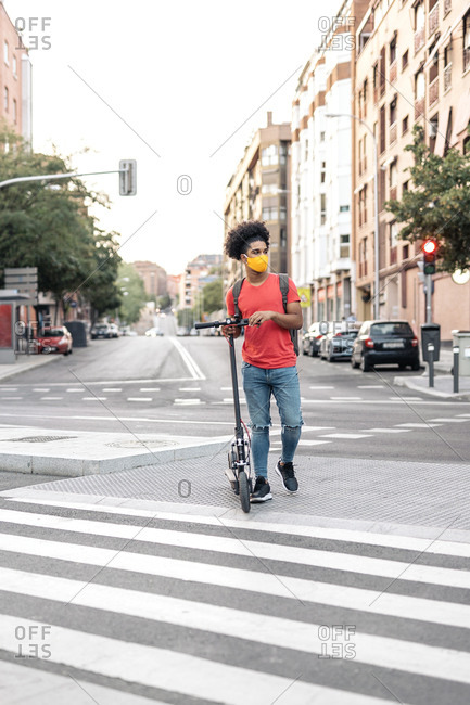 Young African American boy wearing face mask crossing a pedestrian crossing with electric scooter