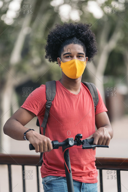 Happy teen black boy wearing face mask due to covid19 and looking at camera while riding an electric scooter