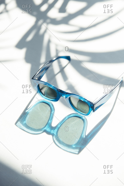 Blue sun glasses on white surface with reflection and shadows