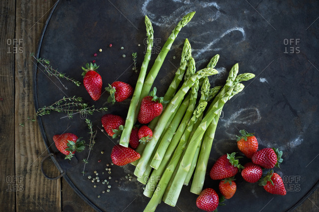 Thyme- peppercorn- asparagus stalks and fresh strawberries on rustic baking sheet