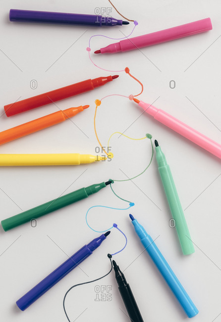 Colorful felt tip pens connected with curved lines