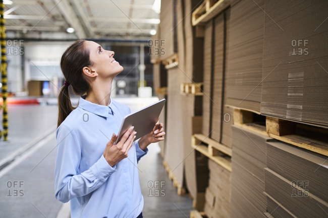 Businesswoman with tablet in a factory warehouse checking stock