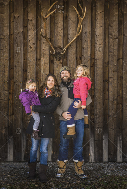 Portrait of a smiling family in front of a cabin with deer antlers