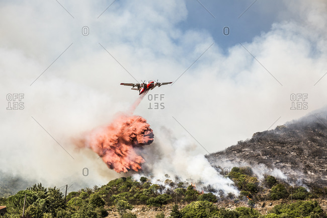 Aerial fire fighting aircraft dropping load of flame retardant on wildfire- Corsica- France