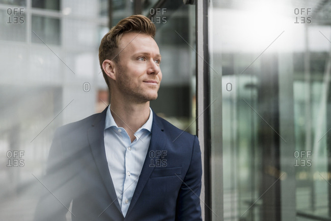 Confident businessman wearing suit looking away in city
