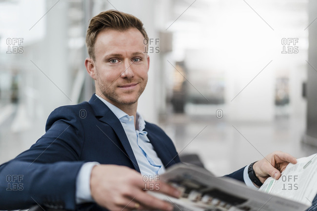 Smiling businessman reading newspaper while sitting in city