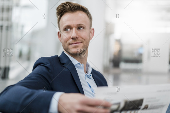 Smiling businessman with newspaper looking away while sitting in city