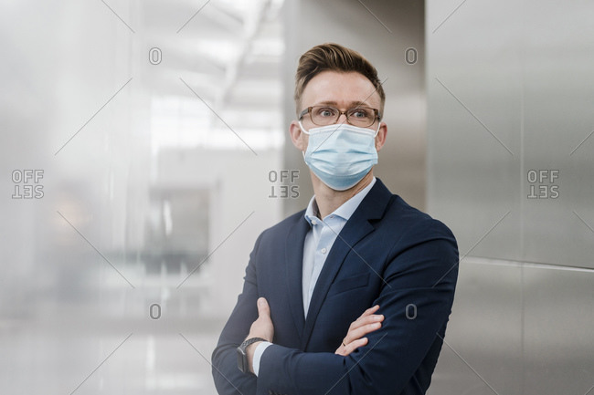 Businessman with arms crossed wearing face mask in city