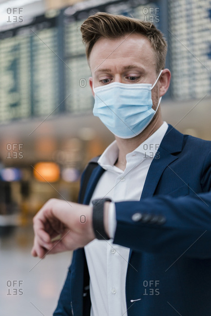 Businessman checking the time while wearing face mask in city